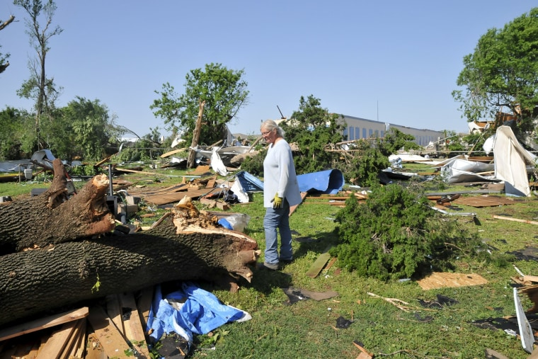 Darla Titus looks through debris in her backyard the morning after a tornado in Oklahoma City, Okla., May 7, 2015. (Photo by Nick Oxford/Reuters)