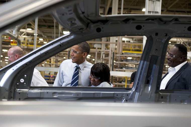 President Barack Obama (C) hugs an assembly line worker as he tours through the Chrysler Auto Plant in Detroit, Mich., July 30, 2010.