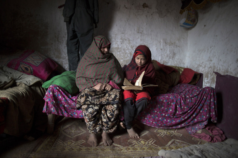 Tadjroshan, 40, poses for a photograph with her daughter Ayman, 12, at their house in a slum on the outskirts of Islamabad February 4, 2014. (Photo by Zohra Bensemra/Reuters)