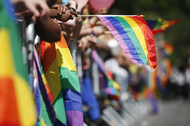 The sidewalks are filled with rainbow flags as revelers celebrate Gay Pride.