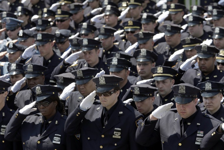 Police officers salute as the procession for New York City Police officer Brian Moore passes after his funeral mass, May 8, 2015, at the St. James Roman Catholic church in Seaford, N.Y. (Photo by Mary Altaffer/AP)