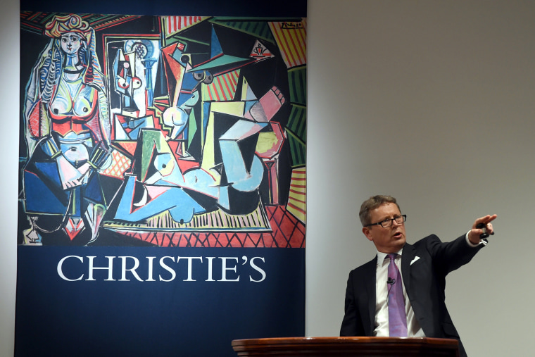 """Auctioneer Jussi Pylkkanen takes bids on the Picasso masterpiece """"Les Femmes d'Alger (Version O)"""" at Christie's in New York City on May 11, 2015. (Photo by Timothy A. Clary/AFP/Getty)"""