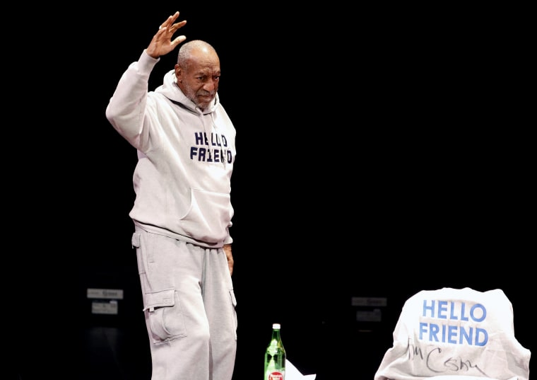 Comedian Bill Cosby waves as he walks onstage for a performance at the Buell Theater in Denver, Saturday, Jan. 17, 2015. (Photo by Brennan Linsley/AP)