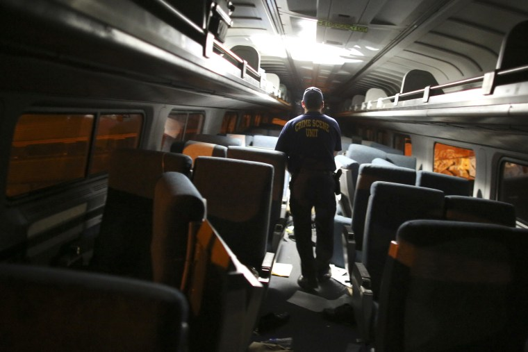 A crime scene investigator looks inside a train car after an Amtrak train wrecked, killing eight people, May 12, 2015, in Philadelphia. (Photo by Joseph Kaczmarek/AP)