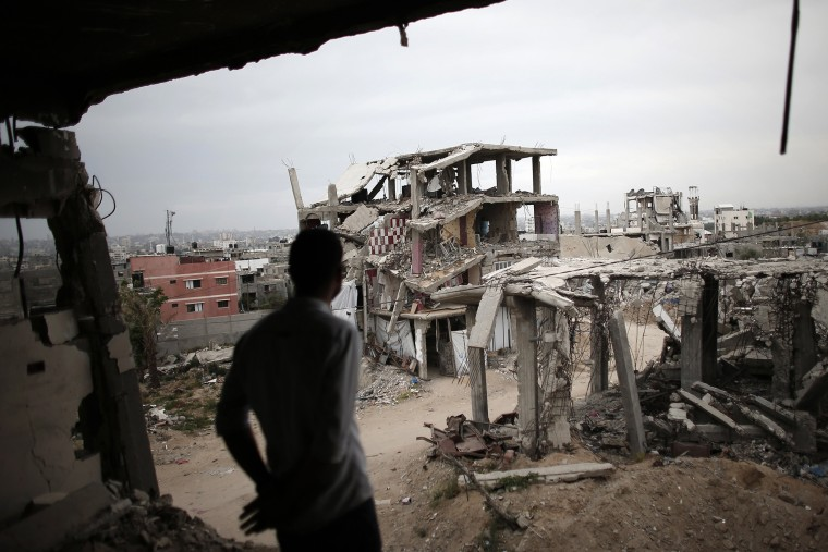 A Palestinian man stands amid the rubble looking at a building opposite to him, on May 11, 2015, which was destroyed during the 50-day war between Israel and Hamas militants in the summer of 2014, in the Eastern Gaza City Shujaiya neighborhood.
