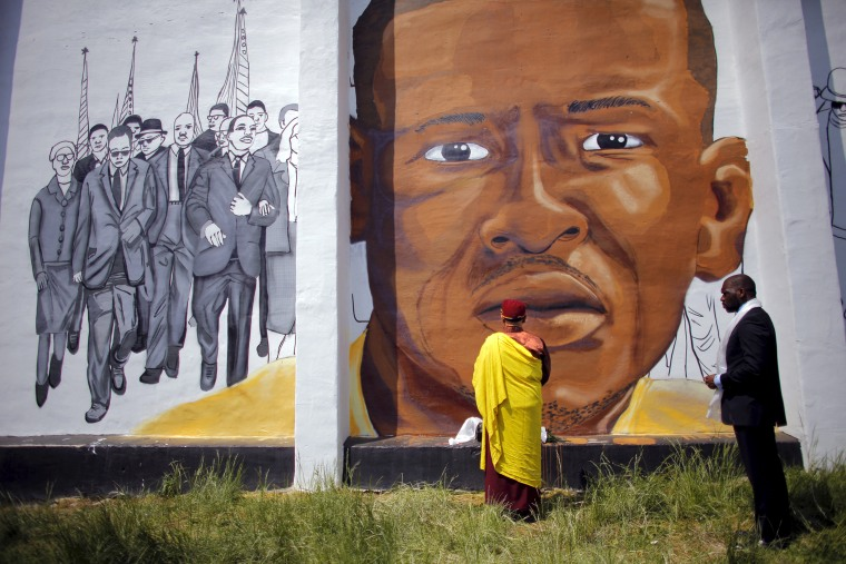 Gyalwang Drukpa, a Buddhist leader from South Asia, prays in front of a mural of Freddie Gray in Baltimore, Md., May 7, 2015. (Photo by Carlos Barria/Reuters)