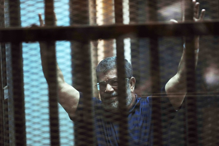 Ousted Egyptian President Mohammed Morsi raises his hands as he sits behind glass in a courtroom in Egypt on May 16, 2015. (Photo by Ahmed Omar/AP)