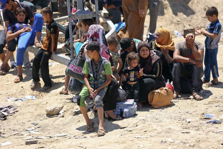 Displaced Iraqis from Ramadi rest before crossing the Bzebiz bridge after spending the night walking towards Baghdad, as they flee their hometown on May 16, 2015. (Photo by Hadi Mizban/AP)