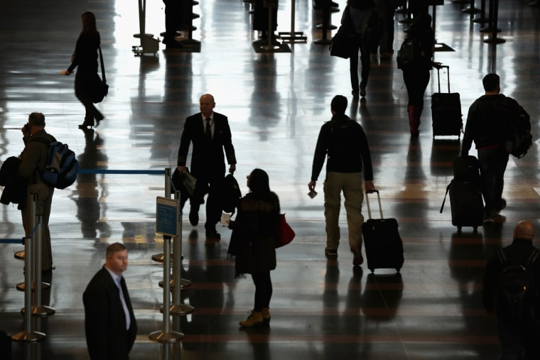 Travelers arrive at an airport. (Photo by Alex Wong/Getty)