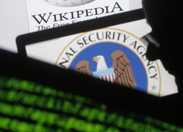 A man is seen near cyber code and the US National Security Agency logo in this photo illustration taken in Sarajevo March 11, 2015. (Photo by Dado Ruvic/Reuters)