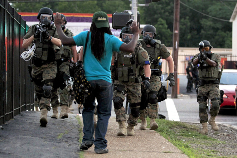 In this Aug. 11, 2014 file photo, police wearing riot gear walk toward a man with his hands raised in Ferguson, Mo. (Photo by Jeff Roberson/AP)