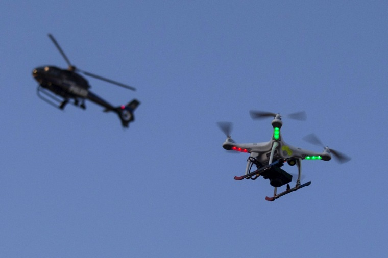 A police helicopter flies past a UAV drone Quadcopter which was flying over a post-march street celebration in west Baltimore, Md., May 2, 2015. (Photo by Adrees Latif/Reuters)