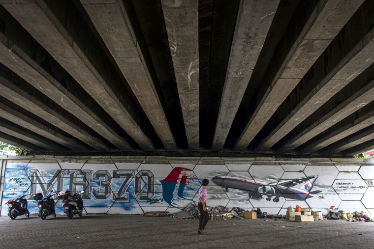 A man walks past MH370 related street art under a flyover in Kuala Lumpur, Malaysia on March 6, 2015. (Photo by Joshua Paul/AP)