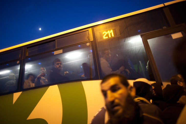 Palestinians board a bus as a new line is made available by Israel to take Palestinian workers from the Israeli army crossing of Eyal, near the West Bank town of Qalqilya, into the Israeli cities, on March 4, 2013. (Photo by Uriel Sinai/Getty)