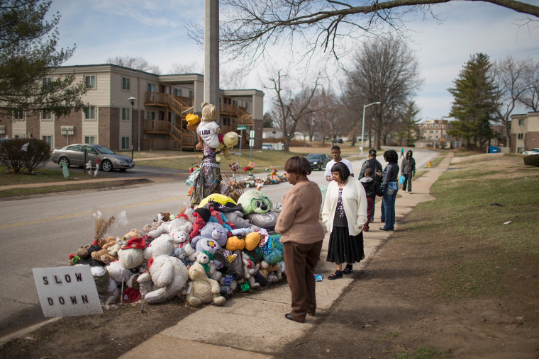 Visitors look over a memorial to Michael Brown outside the Canfield Green apartments where he was shot and killed by a police officer last August on March 14, 2015 in Ferguson, Mo. (Photo by Scott Olson/Getty)