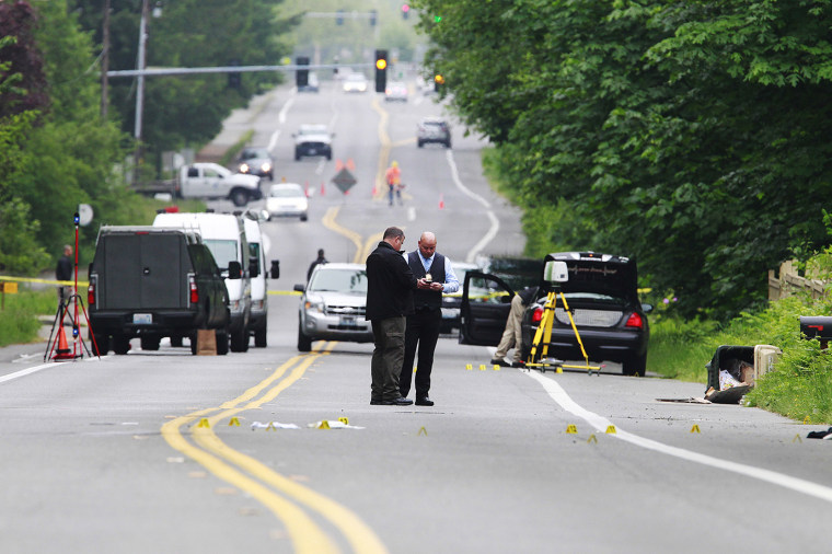 Investigators comb the scene of an officer-involved shooting on May 21, 2015 in Olympia, Wash. (Photo by Steve Bloom/The Olympian/AP)