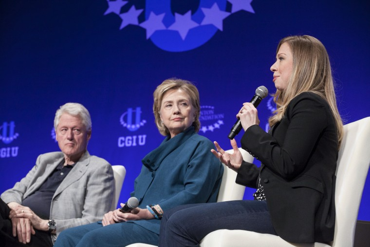 Former President Bill Clinton and former Secretary of State Hillary Clinton listen to their daughter and Vice Chair of the Clinton Foundation Chelsea Clinton in Tempe, Arizona on March 22, 2014. (Photo by Samantha Sais/Reuters)