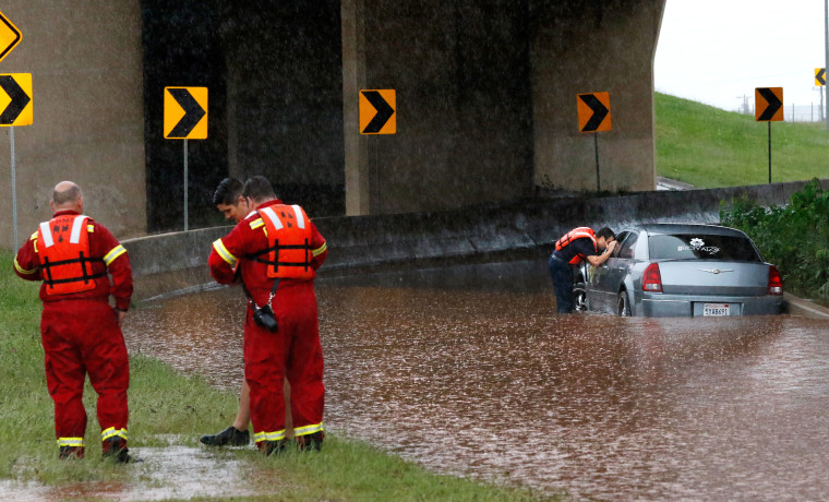 A firefighter looks into the window of a partially submerged car, checking to see if anyone is inside, May 23, 2015, in Oklahoma City. (Photo by Jim Beckel/The Oklahoman/AP)