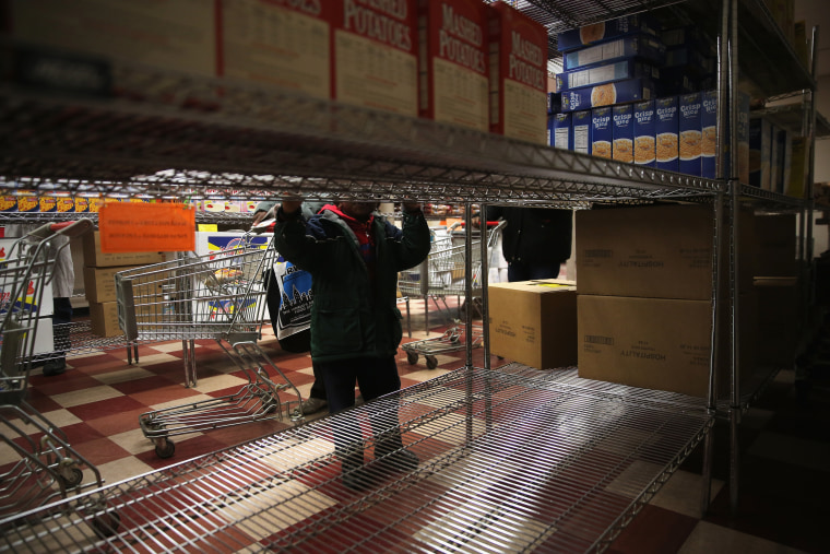 A child accompanies his grandmother choosing free groceries at a food pantry run by the Food Bank For New York City on Dec. 11, 2013 in New York City. (John Moore/Getty)