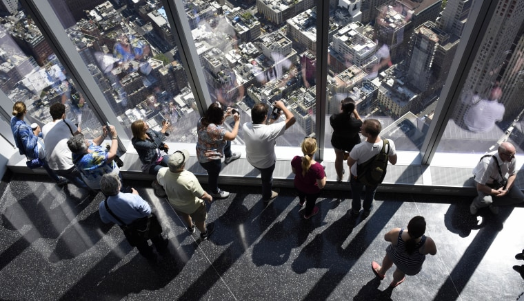 Visitors look out over city streets from the One World Observatory at One World Trade Center in New York, N.Y. on May 29, 2015. (Photo by Justin Lane/EPA)