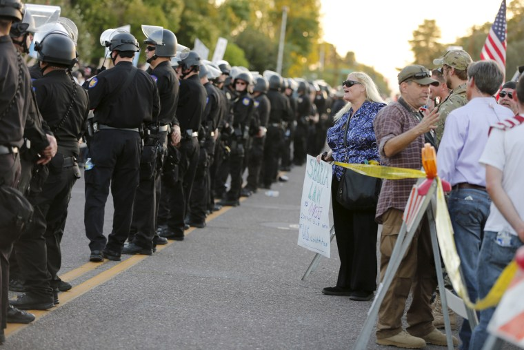 """A police line separates people attending the """"Freedom of Speech Rally Round II"""" from counter demonstrators outside the Islamic Community Center in Phoenix, Ariz. on May 29, 2015. (Photo by Nancy Wiechec/Reuters)"""