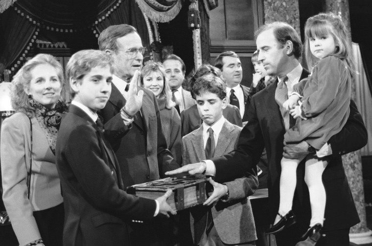 Sen. Joe Biden holds his daughter Ashley while taking a mock oath of office from Vice President George Bush during a ceremony on Capitol Hill, Jan. 3, 1985. Biden's sons Beau and Hunter hold the bible during the ceremony. (Photo by Lana Harris/AP)
