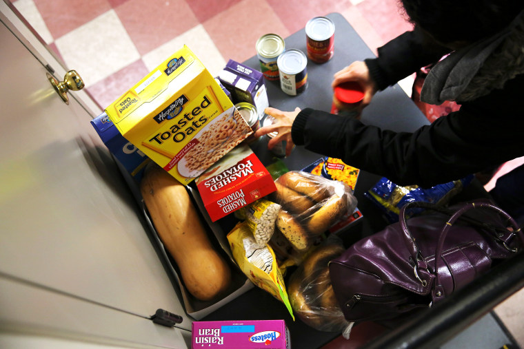People receive free groceries at a food pantry run by the Food Bank For New York City, Dec. 11, 2013. (Photo by John Moore/Getty)