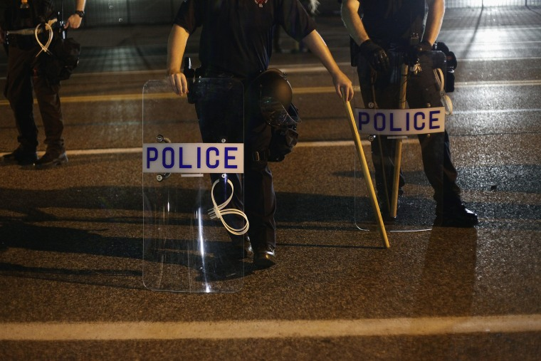 Police officers in riot gear stand in position as demonstrators protest the shooting death of Michael Brown, in Ferguson, Mo., Aug. 19, 2014. (Photo by Joshua Lott/Reuters)