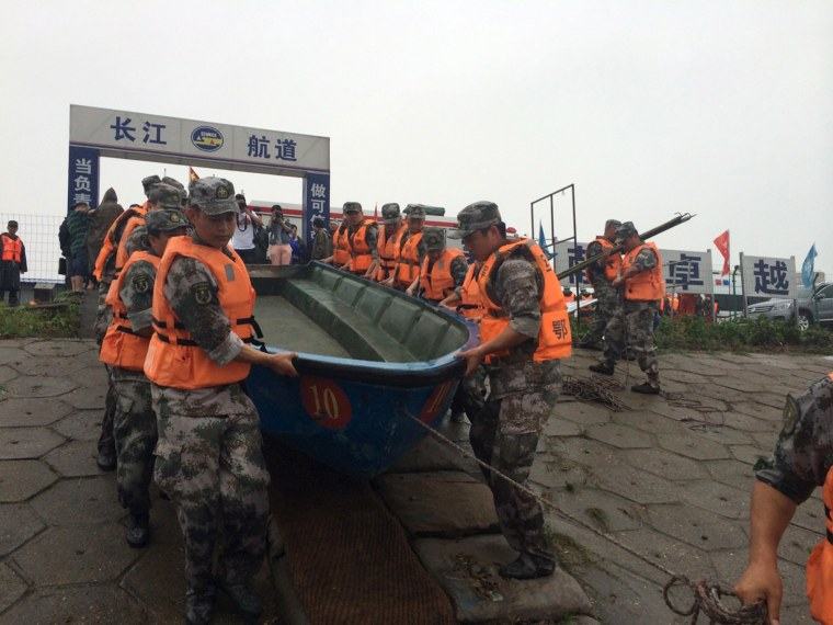 Rescue workers carry a boat as they conduct a search, after a ship sank in the Jianli section of the Yangtze River, Hubei province, China, June 2, 2015. (Photo by Chen Zhuo/Yangzi River Daily/Reuters)