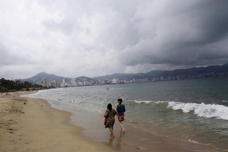Tourists walk along a beach as dark clouds brought by hurricane Blanca are seen in Acapulco, state of Guerrero, on June 4, 2015. (Photo by Claudio Vargas/Stringer Mexico/Reuters)