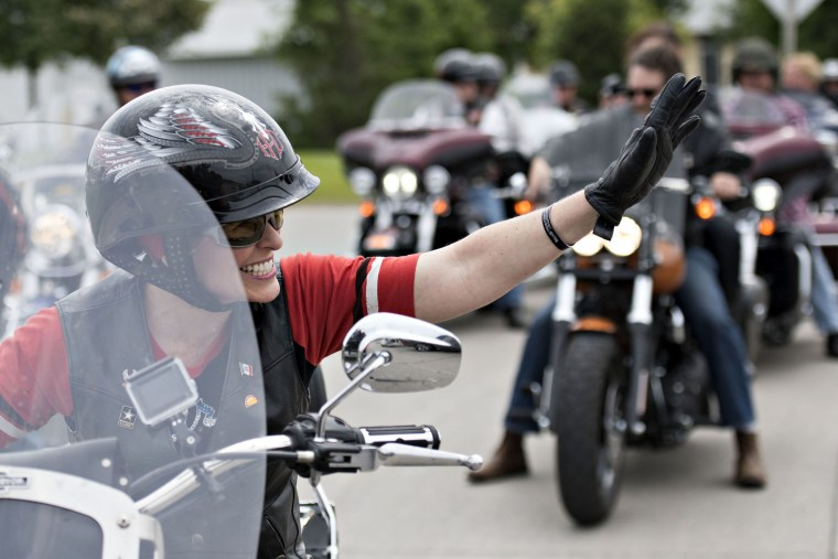 Senator Joni Ernst, a Republican from Iowa, waves to supporters as she rides the lead bike in a group motorcycle ride in Des Moines, Iowa on June 6, 2015. (Photo by Daniel Acker/Bloomberg/Getty)