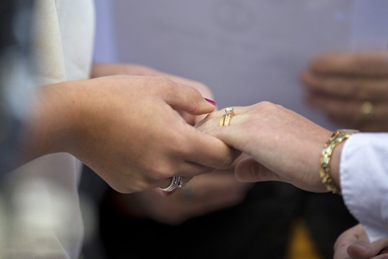 Two women hold hands after exchanging wedding rings during a ceremony. (Photo by Manuel Balce Ceneta/AP)