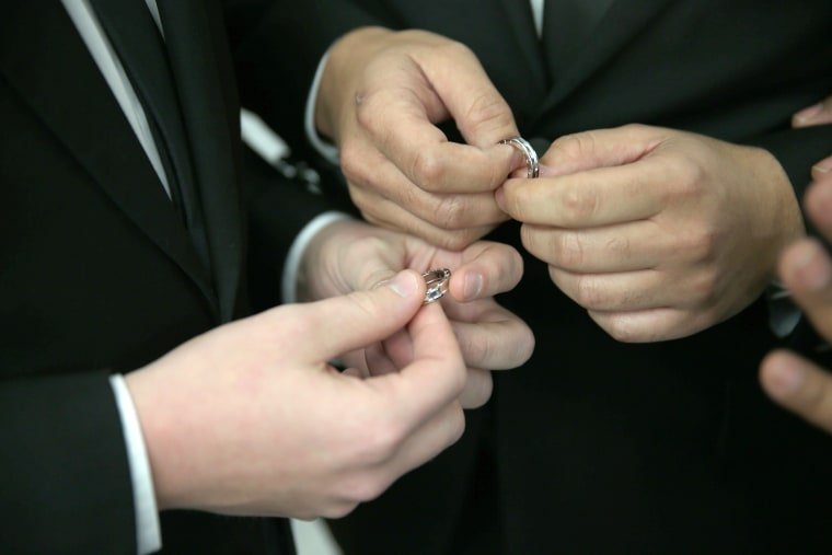 A couple exchange rings as they are wed during a wedding ceremony. (Photo by Joe Raedle/Getty)