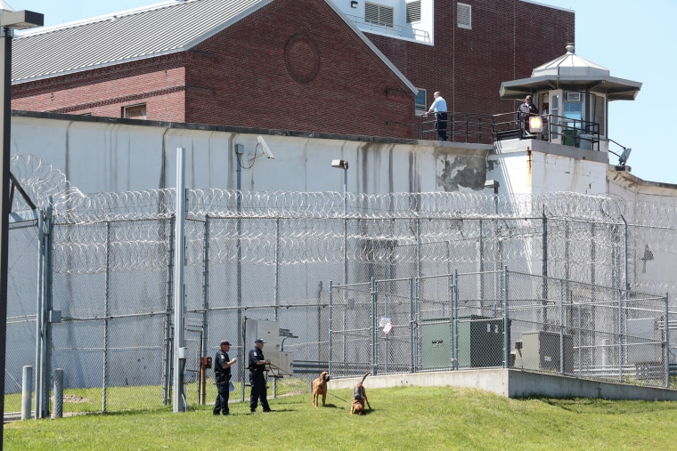 Law enforcement officers with bloodhounds stand guard at one of the entrances to the Clinton Correctional Facility in Dannemora, N.Y. on Saturday, June 6, 2015. (Photo by Gabe Dickens/Press-Republican/AP)