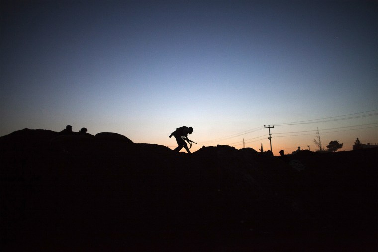 The silhouette of an armed fighter of the Committees for the Protection of the Kurdish People (YPG) is seen as runs to take position along the front line on October 16, 2013 in the Syrian town of Ras al-Ain, close to the Turkish border.