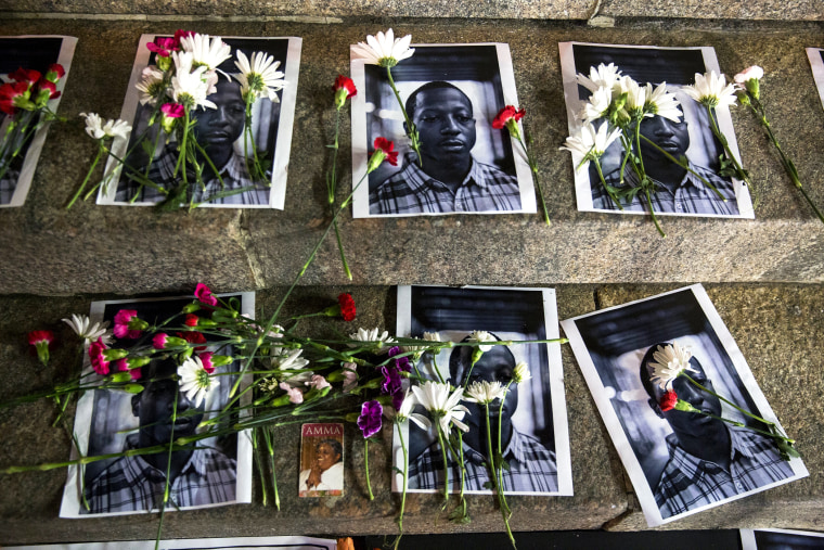 Flowers rest on top of pictures of Kalief Browder in New York June 11, 2015. (Photo by Lucas Jackson/Reuters)