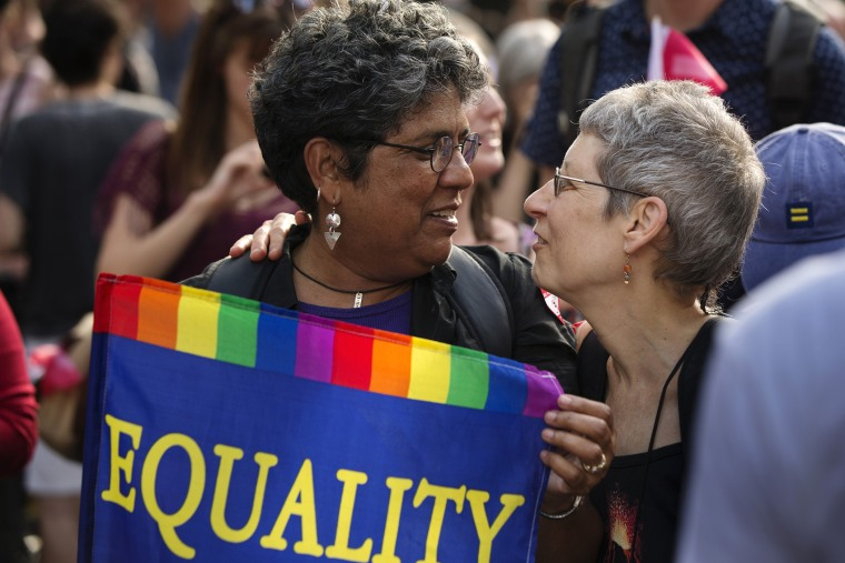 "Carmen Castro carries an ""Equality"" flag as she greets Wind Vogel while celebrating the U.S. Supreme Court ruling against the Defense of Marriage Act outside the Stonewall Inn, June 26, 2013. (Photo by Lucas Jackson/Reuters)"