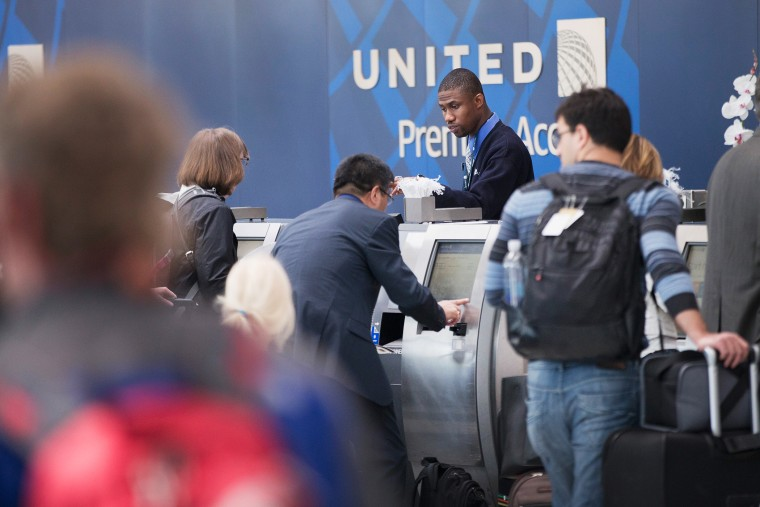 Passengers check-in for flights with United Airlines. (Photo by Scott Olson/Getty)