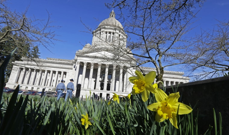 Early daffodils bloom as two Washington State Patrol troopers walk toward the U.S. Capitol, Feb. 17, 2015, in Olympia, Washington. (Photo by Ted S. Warren/AP)