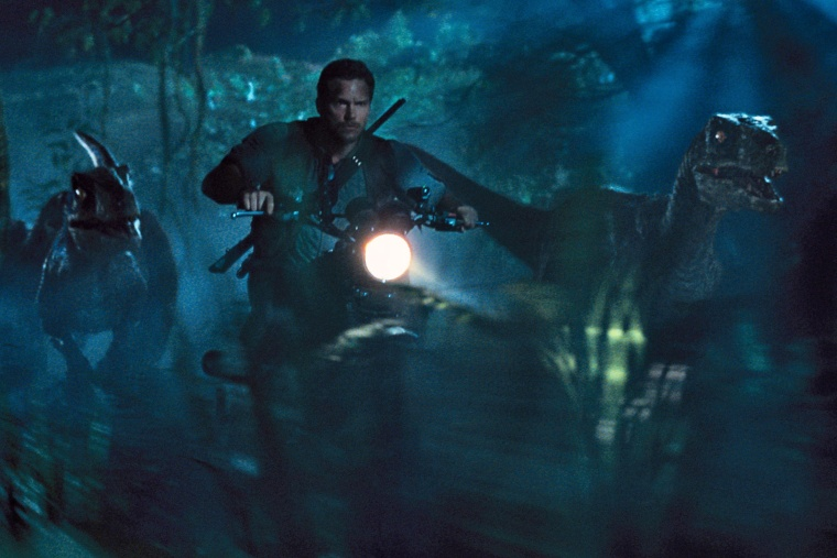 """This photo provided by Universal Pictures shows, Chris Pratt as Owen leading the raptors on a mission in a scene from the film, """"Jurassic World,"""" directed by Colin Trevorrow. (Photo by ILM/Universal Pictures/Amblin Entertainment/AP)"""