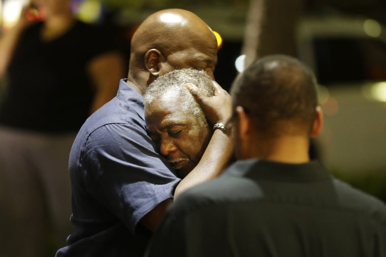 Worshippers embrace following a group prayer across the street from the scene of a shooting, June 17, 2015, in Charleston, S.C. (Photo by David Goldman/AP)