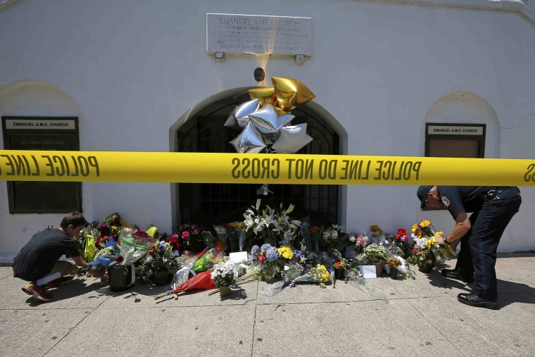 A boy helps a police officer move flowers left behind outside Emanuel African Methodist Episcopal Church after the street was re-opened a day after a mass shooting left nine dead at the church in Charleston, S.C. (Photo by Brian Snyder/Reuters)