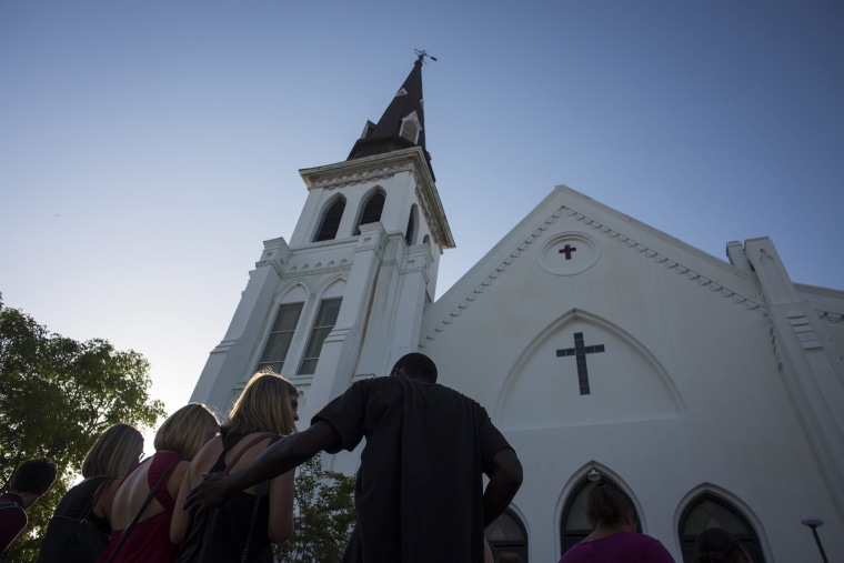 People comfort each other during a vigil at the memorial site outside of the Emanuel African Methodist Episcopal (AME) Church where nine people were murdered in Charleston, S.C., June 18, 2015. (Photo by John Taggart/EPA)