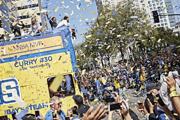 Steph Curry waves to the cheering crowd during the Golden State Warriors' victory parade down Broadway in Oakland, Calif. on June 19, 2015. (Photo by Balazs Gardi for MSNBC)