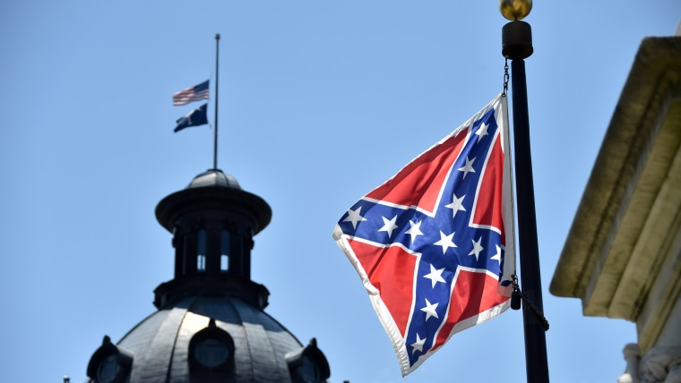 The South Carolina and American flags flying at half-staff behind the Confederate flag erected in front of the State Congress building in Columbia, S.C., June 19, 2015. (Photo by Mladen Antonov/AFP/Getty)