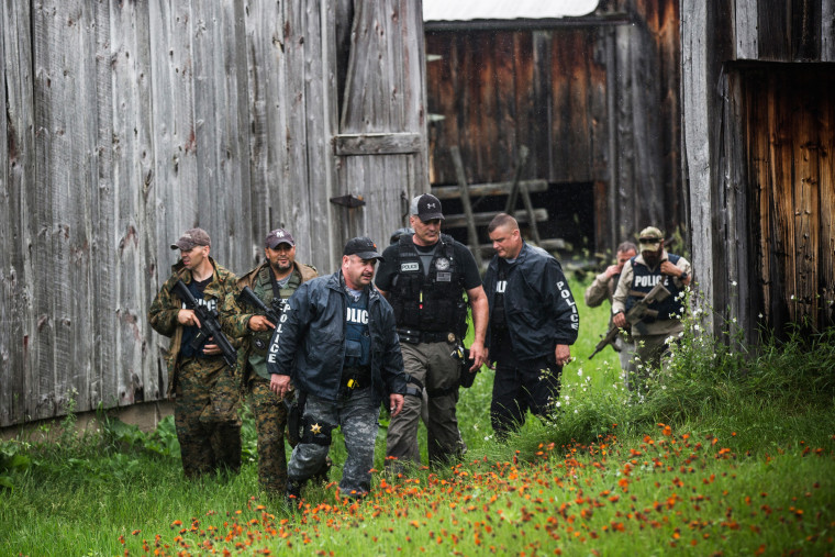 A task force of U.S. Marshalls and police officers go door to door searching for two escaped convicts on June 16, 2015 outside Dannemora, N.Y. (Photo by Andrew Burton/Getty)