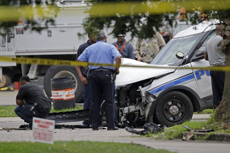 Investigators look over a New Orleans Police department vehicle in which one officer was shot and killed while transporting a prisoner in New Orleans, La. on June 20, 2015. (Photo by Gerald Herbert/AP)
