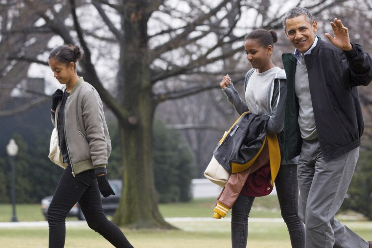 President Barack Obama, right, waves to the media with daughters Sasha and Malia, left, on Jan. 5, 2014. (Photo by Jacquelyn Martin/AP)