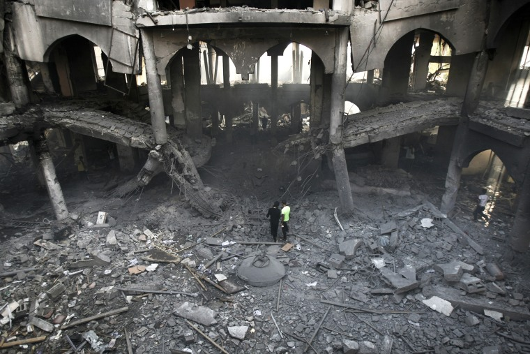 Palestinians inspect the damage of a Rafah commercial center after an Israeli strike in Rafah, in the southern Gaza Strip, Aug. 24, 2014. (Photo by Eyad Baba/AP)