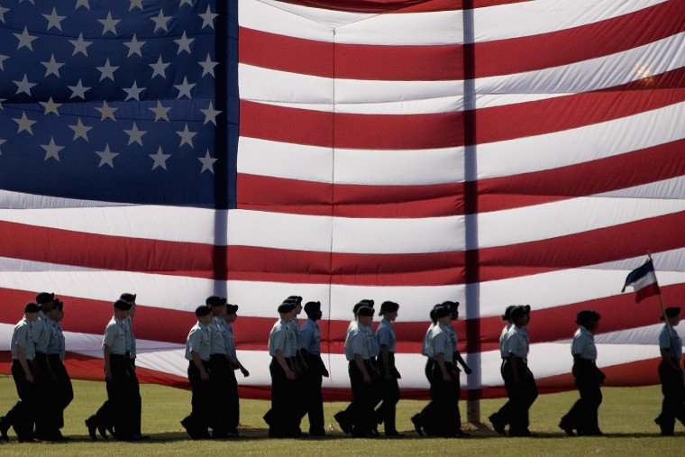 Troops march past a large American flag as they graduate from Basic Combat Training at Fort Jackson, S.C., Nov. 2, 2007. (Photo by Paul J. Richards/AFP/Getty)